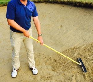 golfspieler harkt im Bunker